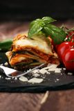 Serving of spicy traditional Italian beef lasagne in a restaurant. Bolognese sauce topped with basil leafs royalty free stock photos