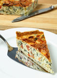 Serving spinach beet quiche. Serving a piece of delicious quiche made from spinach beet (aka Swiss chard or sea kale beet), leek and tomato baked in a cheesy egg Royalty Free Stock Photos