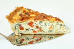 Serving spinach quiche horizontal. Horizontal view of a piece of delicious quiche made from spinach beet (aka Swiss chard or sea kale beet), leek and tomato Stock Photo