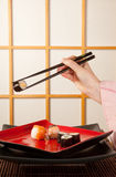Serving sushi with chopsticks Stock Photos