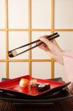 Serving sushi with chopsticks Stock Photos