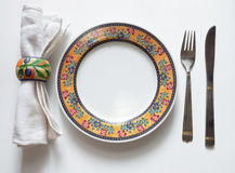 Serving of table. A dessert dish, knife, fork and serviette, costs on a white table Stock Photos
