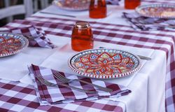 Serving on the table in the restaurant: plates, glasses and napkins stock photo