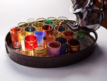 Serving tea Middle Eastern style. Colorful glasses in a metal tray being filled with tea from a silver teapot Stock Photo