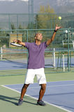 Serving a tennis ball. Into net. young man posing Stock Images
