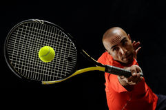 Serving a tennis ball. A portrait of a tanned sportive tennis player with a racket against black background Royalty Free Stock Images