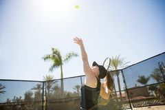 Serving tennis ball on sunny day. Fit young woman tennis player serving ball whilst practising on court during a sunny day Stock Photos