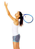 Serving tennis woman. Healthy active mixed race female throws an imaginery tennis ball in the air and pretends to serve in studio Stock Image
