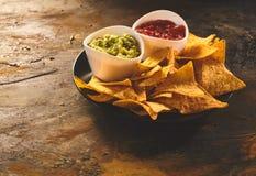 Serving of tortilla chips, guacamole and salsa dip Stock Photos