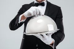 Serving tray with cloche holded by butlers hands in gloves. Closeup of serving tray with metal cloche holded by butlers hands in gloves Royalty Free Stock Photo