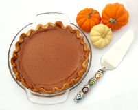 Serving up pie. Pumpkin pie, pie server and mini pumpkins royalty free stock photography