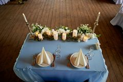 Serving wedding table.Starched white napkins , led candle and flowers on a blue tablecloth. The table of the newlyweds Royalty Free Stock Images