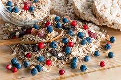 Serving of wild berries cereal, crispbread bulk on wooden table Stock Photos