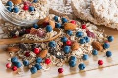 Serving of wild berries cereal, crispbread bulk on wooden table Stock Images