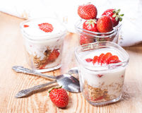 Serving of yogurt with granola and strawberries. Yougrt, strawberries and granola in glass jars Royalty Free Stock Image