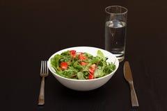 Servir com salada clara com tomates e um vidro da água Foto de Stock