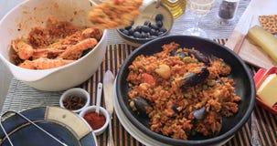 Servir une partie de Paella espagnole de fruits de mer : moules, crevettes roses de roi, langoustine, aiglefin clips vidéos