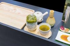 Servire del latte del tè verde del ghiaccio con tè verde caldo Fotografie Stock