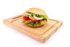Servire dell'hamburger del pollo sullo spezzettamento del legno a pezzi Fotografie Stock