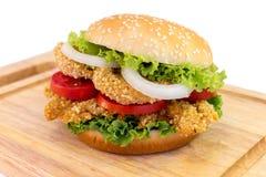 Servire dell'hamburger del pollo sullo spezzettamento del legno a pezzi Immagine Stock