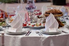 Servito per una tabella di banchetto Vetri di vino con i tovaglioli, vetri ed insalate Fotografia Stock Libera da Diritti