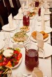 Servito per una tavola di banchetto con i vetri e tovaglioli ed insalate bianchi Fotografia Stock
