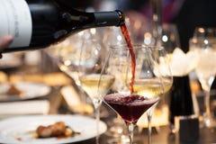 Servitrins häller rött vin i exponeringsglaset på tabellen i restaurang Royaltyfri Foto