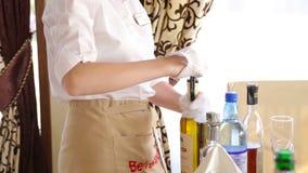 Servitrins (precis händer som ska ses) poppar korken av en flaska av rött vin stock video