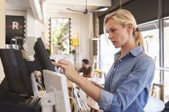 Servitris At Cash Register i coffee shop royaltyfria bilder