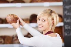 Servitris Keeping Sweet Bread på hylla i kafé Royaltyfri Bild