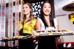 Servitris med sushi i asiatisk restaurang Fotografering för Bildbyråer