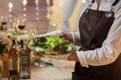 Servitris med tabellen för bankett för portion för grönsakmatmaträtt royaltyfri fotografi