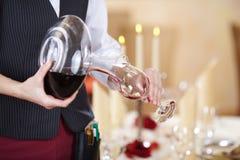 Servitris Pouring Red Wine i vinglas Royaltyfria Foton