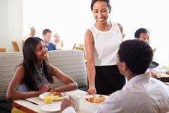 Servitris Serving Couple Breakfast i hotellrestaurang royaltyfri bild