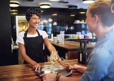 Servitris Serving Glasses av vin till kunden Arkivbild