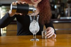 Servitris som gör en drink Fotografering för Bildbyråer
