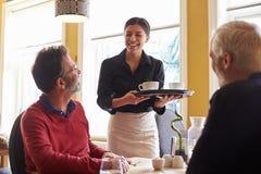 Servitris som kommer med kaffe till ett manligt par på en restaurang Arkivbild