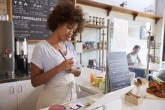 Servitris som ner upp skriver en beställning på en coffee shop, slut Arkivfoton