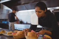 Servitris som ordnar korgar med mat i kafé Arkivbilder