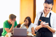 Servitris som skriver en beställning med studenter som använder bärbara datorn på coffee shop Royaltyfri Foto