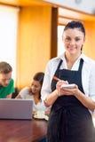 Servitris som skriver en beställning med studenter som använder bärbara datorn på coffee shop Royaltyfri Fotografi