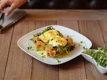 Servitris som tjänar som en lunchnärbild Tjuvjagade ägg på en tabellbackg Arkivfoto