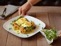 Servitris som tjänar som en lunchnärbild Tjuvjagade ägg på en tabellbackg Royaltyfri Fotografi