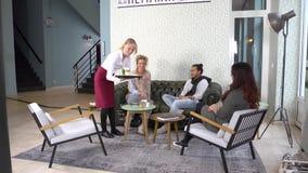 Servitrisportiondrinkar till en grupp av kunder av ett kafésammanträde i ett retro utformat vardagsrumområde av stången stock video