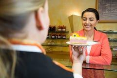 Servitrisportionkaka till kunden i caf� Fotografering för Bildbyråer