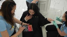 Servizi veloci, manicure facente femminile felice durante il trucco e acconciature in studio