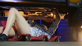 Servizio automatico ragazza del meccanico che si trova sotto l'automobile e che lo ripara Impianti con una chiave archivi video