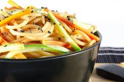 Servizio degli spaghetti con le carote e la salsa di soia e dello zucchini immagini stock libere da diritti