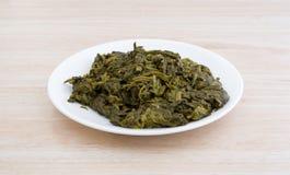 Servizio degli spinaci inscatolati su un piatto bianco Fotografia Stock