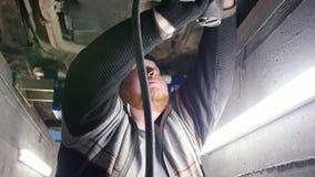 Servizio dell'automobile Condizione spessa dell'uomo del meccanico nel pozzo di ispezione e lavorare con lo strumento automatico video d archivio